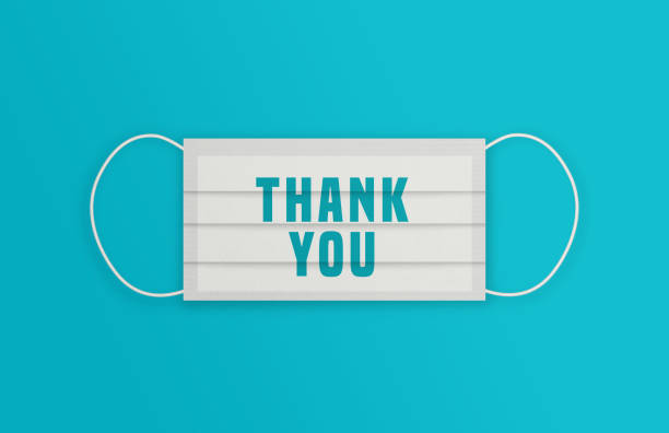 White Protective Mask with Thank You message over the blue background. stock photo