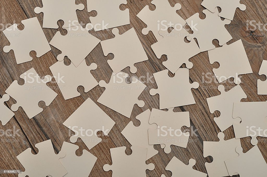 White puzzle pieces on a wooden background stock photo