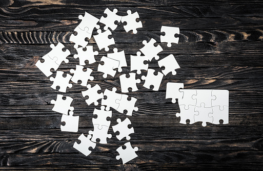 white puzzle pieces on dark table