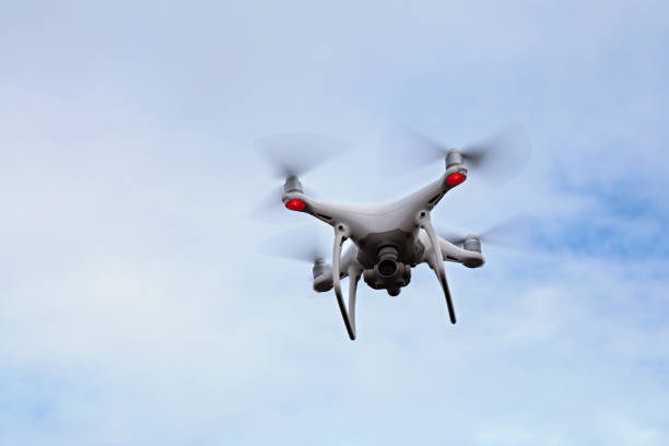 White quadcopter drone with photo camera Noirmoutier, France - July 27 2017: Close-up on a white quadcopter drone hovering in a cloudy sky above the Passage du Gois in Vendée. Because of the 4k camera and the gimbal used for stability, this kind of drone is ideal for aerial photography and stunning videos. drone point of view stock pictures, royalty-free photos & images