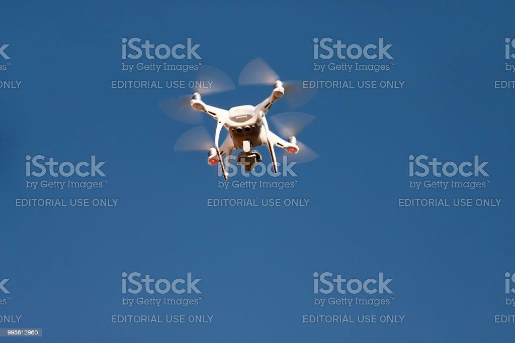Quadrocopter branco DJI fantasma 4 drone mosca céu em segundo plano. Drone moderno está voando no ar, para tirar fotos e gravar imagens de cima. Drone com quatro hélices. - foto de acervo