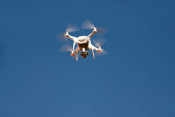 White quadrocopter DJI phantom 4 drone fly on sky in background. Modern drone is flying in air, to take photos and record footage from above. Drone with four propellers. stock photo