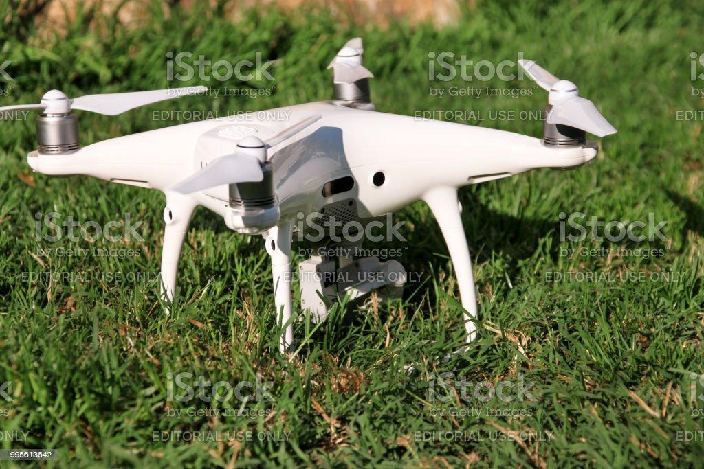 Branco quadrocopter DJI fantasma 4 drone com 4K digital câmera na grama está pronta para decolar para voar no ar para tirar fotos, gravar imagens. Drone com quatro motores. - foto de acervo