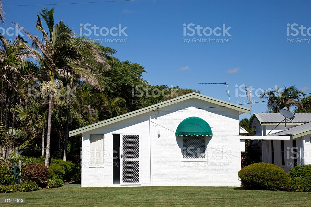 White quaint little cottage house and blue sky stock photo