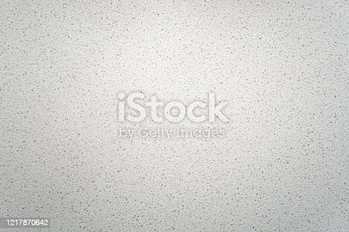 White quartz background countertop. This light background is taken from a bright off-white quartz kitchen counter. The subtle texture can be used as surface or table backdrop graphic design element.