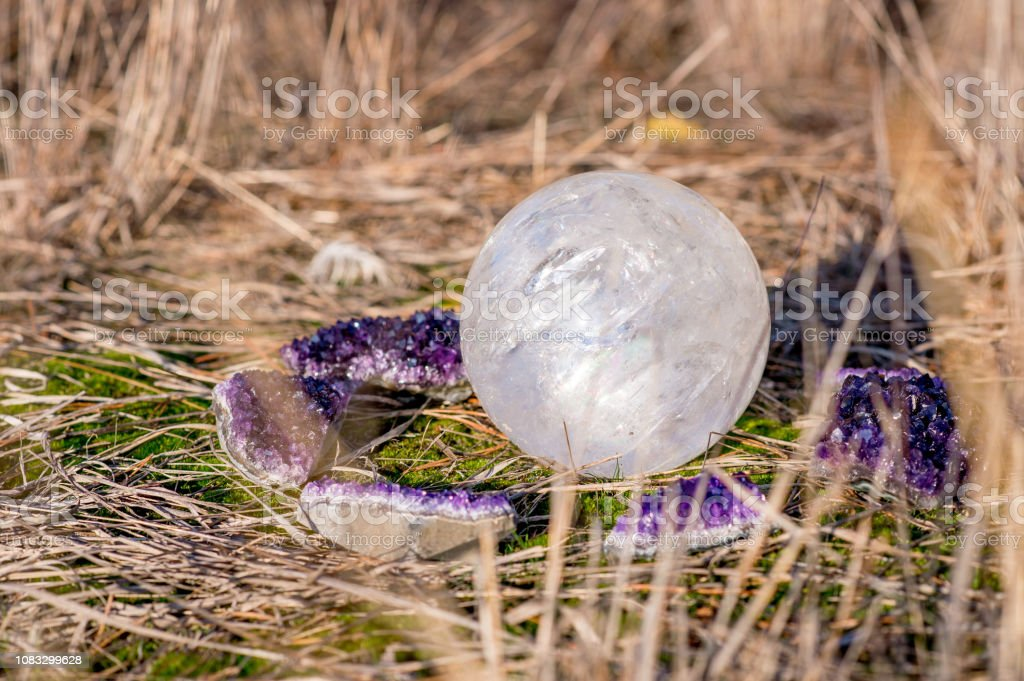Weißer Quarz Kugel umgeben von Amethyst Kristalle – Foto