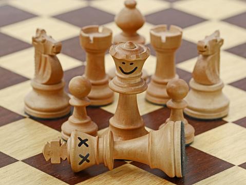 white queen kills white king on chess game, chess crime scene, concept of treachery.