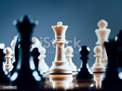Close up of chessmen on chessboard, with the focus on the centrally placed white queen. Shot with Canon EOS 1Ds Mark III.