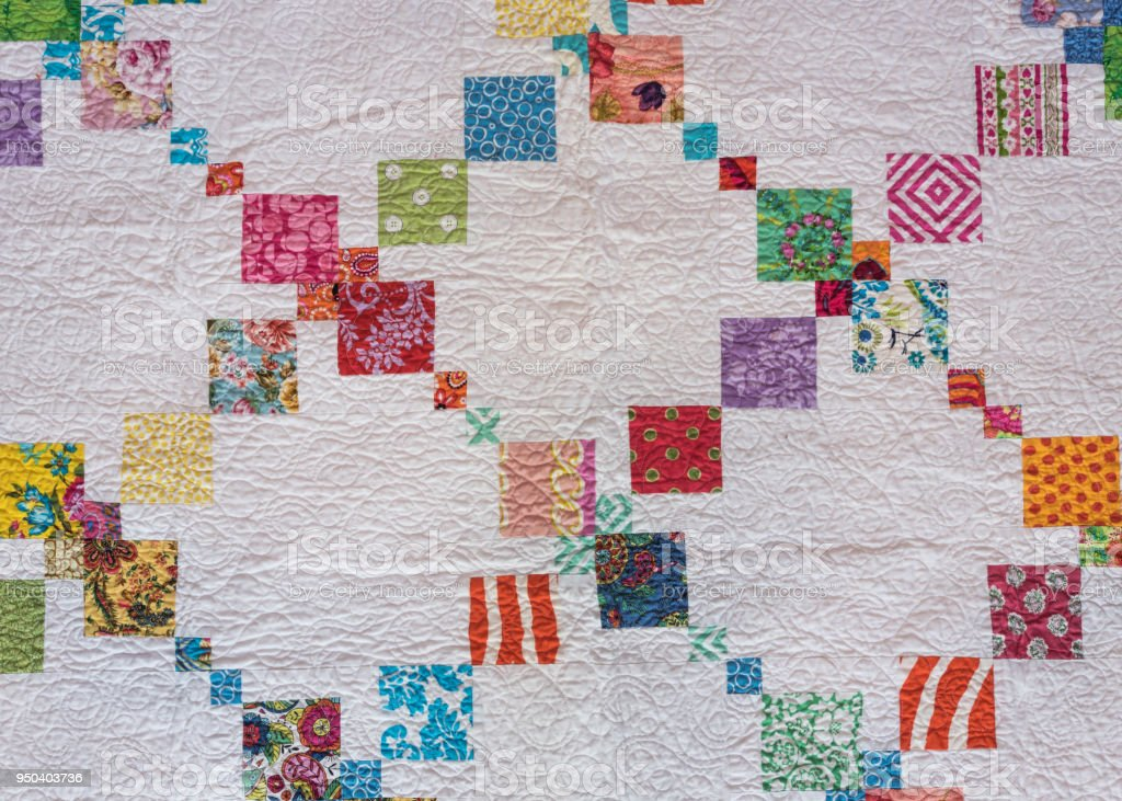 White Quilt with Diagonal Colorful Accents stock photo