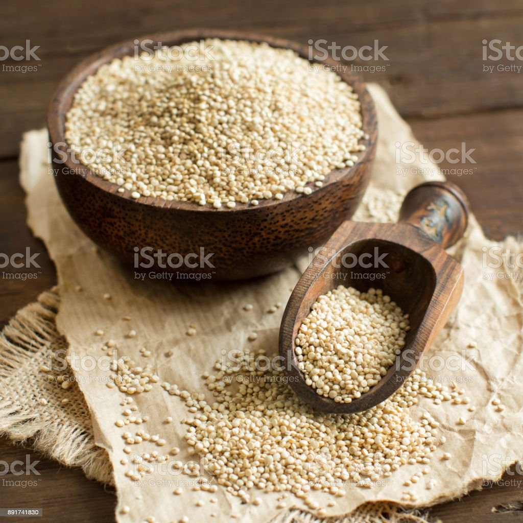 White Quinoa in a bowl with a wooden spoon stock photo