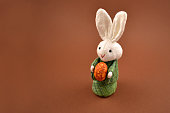 Easter bunny on a brown background. Easter rabbit with egg. Spring decoration images. Easter concept