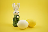 Easter bunny on a yellow background. Easter rabbit with egg. Spring decoration images. Easter concept