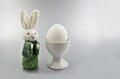 Easter bunny on a silver background. Easter rabbit with egg. Spring decoration images. Easter concept