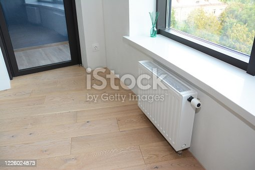 1070686034 istock photo White radiator heating with thermostat for energy saving in unfinished home room repair with balcony door. 1226024873