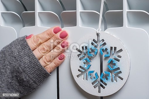 istock White radiator in the house with symbolic snowflake 970740562