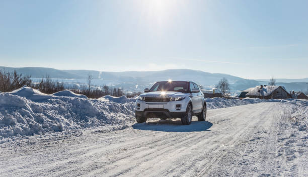 White Range Rover Evoque with a black roof on a winter road on the background of Zhiguli mountains of Samara region, Russia. Clear Sunny day 9 February 2019 White Range Rover Evoque with a black roof on a winter road on the background of Zhiguli mountains of Samara region, Russia. Clear Sunny day 9 February 2019. range rover stock pictures, royalty-free photos & images