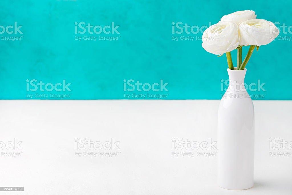 White ranunculus flowers in a ceramic vase stock photo