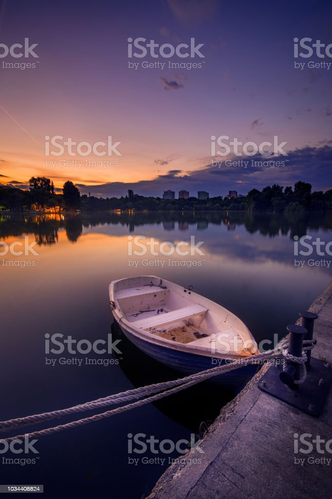White recreational boat at sunset in a park in Romania stock photo
