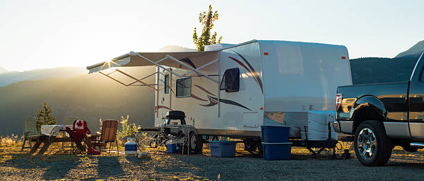 white recreational vehicle parked up at sunset - motorhome stock photos and pictures