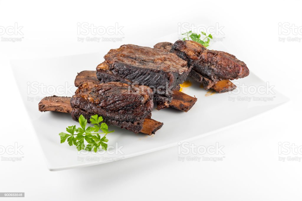 White rectangular plate with three cooked beef ribs stock photo