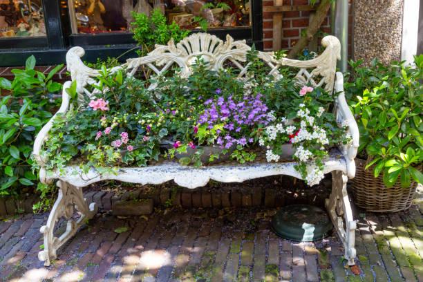 Witte Renaissance Bench geladen met planten foto