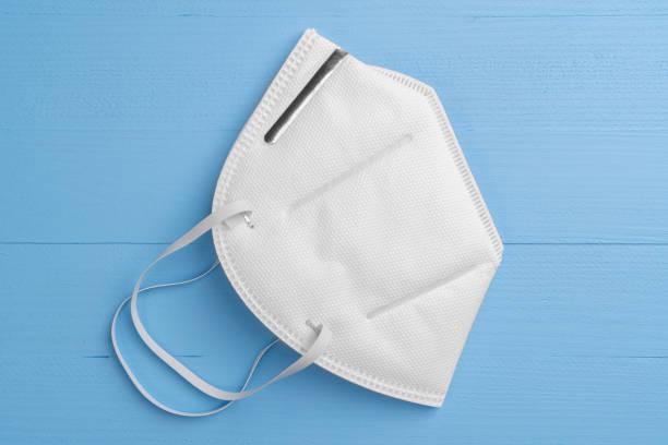 white respiratory mask n95 on a light blue wooden background - ffp2 imagens e fotografias de stock