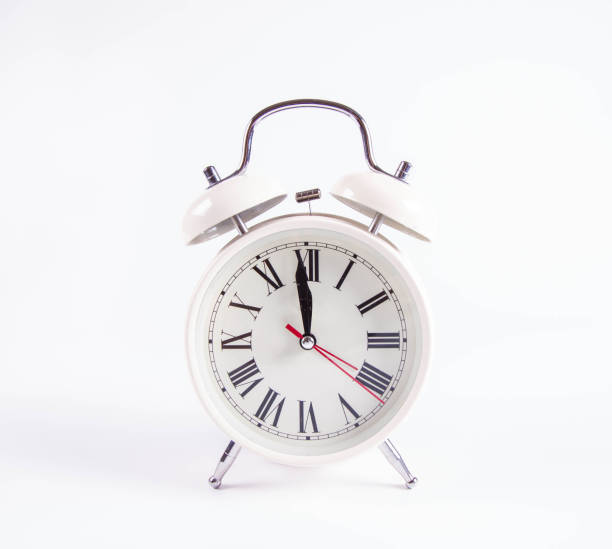 White retro alarm clock at around twelve o'clock White retro alarm clock on a white background at around twelve o'clock midnight stock pictures, royalty-free photos & images