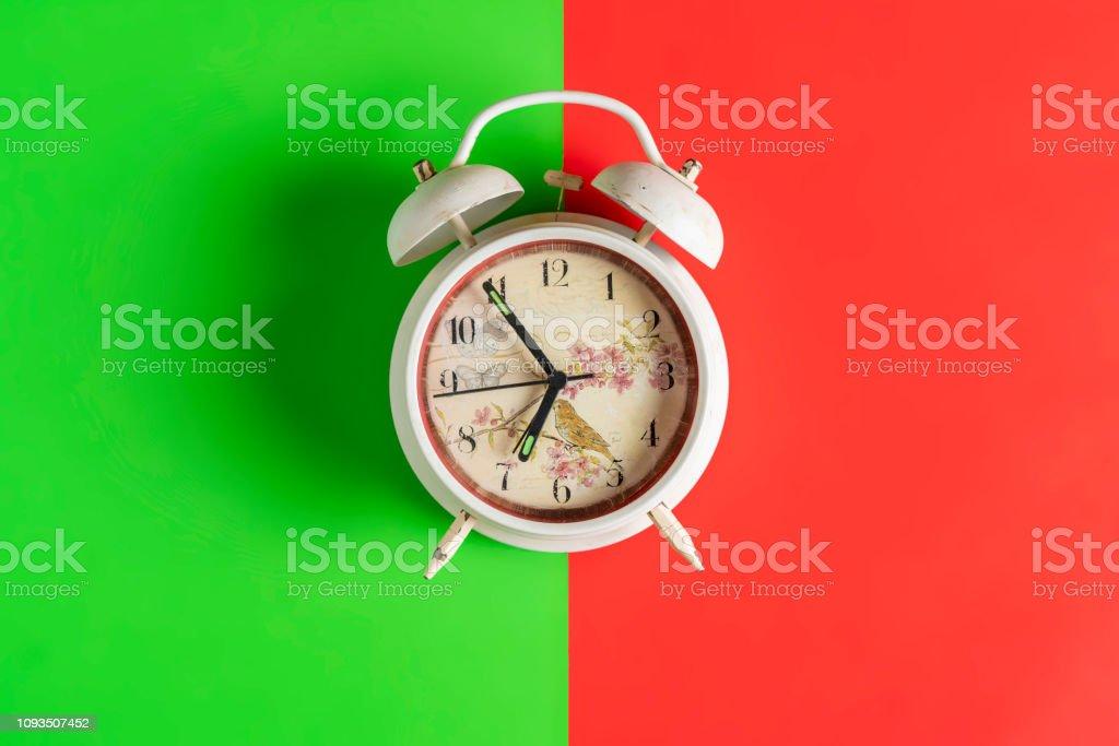 white retro alarm clock idolated on colorful background on wood surface b stock photo