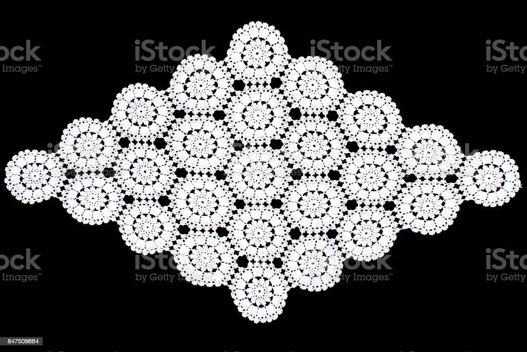 White rhomboid lace tablecloth isolated on black background, circle parttern stock photo