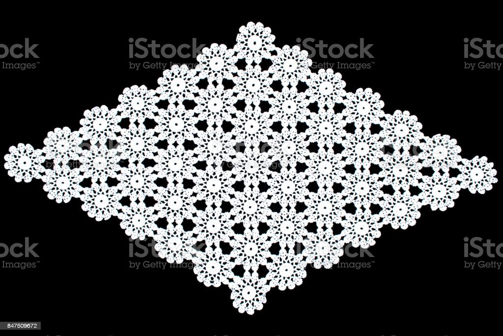 White rhomboid lace tablecloth isolated on black background, close up stock photo
