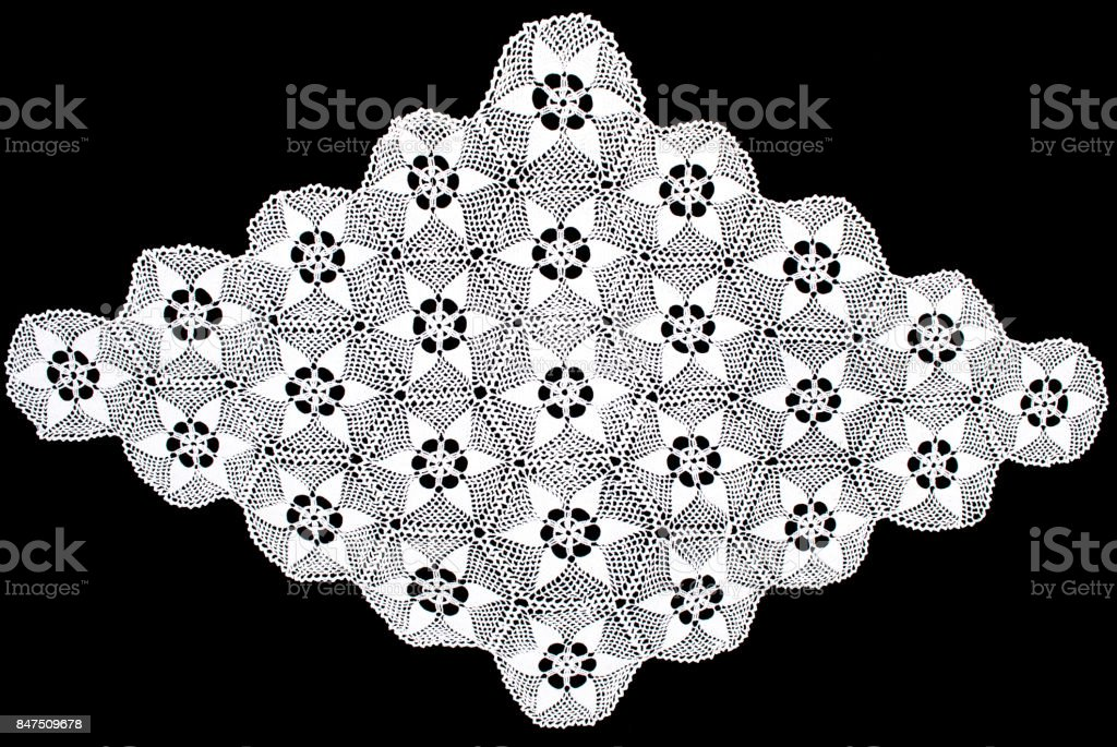White rhomboid lace tablecloth isolated on black background, floral pattern stock photo