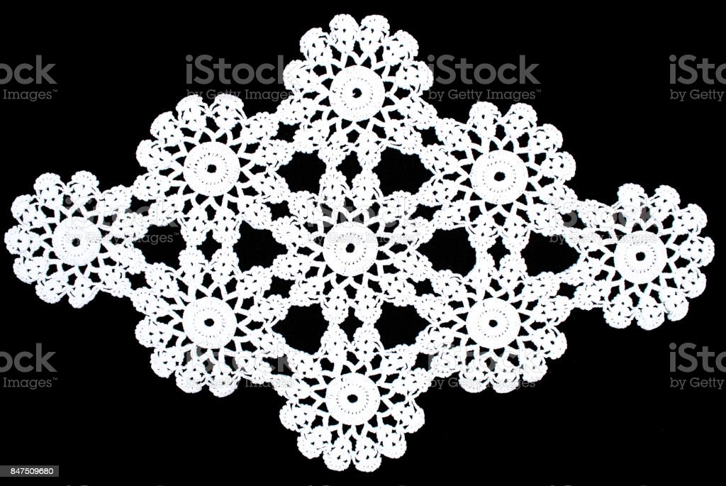 White rhomboid lace tablecloth isolated on black background stock photo