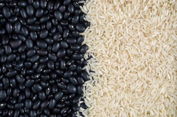 White rice and black beans Raw food, raw black beans, vegan, background, texture, raw white rice, beans and rice. rice cereal plant stock pictures, royalty-free photos & images