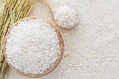istock White rice in bowl and wooden spoon on white rice background 613884840