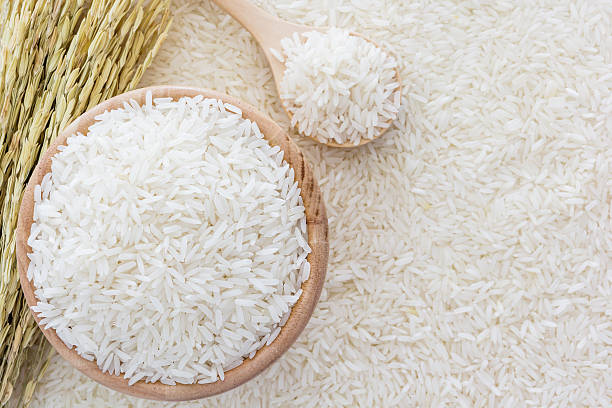 White rice in bowl and wooden spoon on white rice background - foto de stock