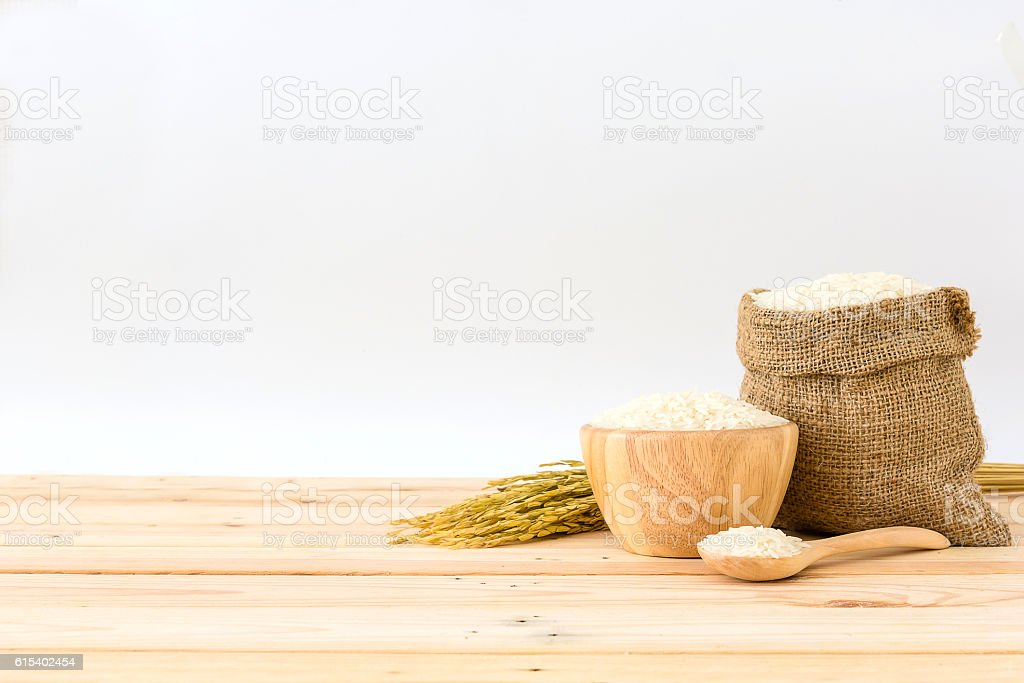 White rice in bowl, bag and rice plant on wooden table - foto de stock
