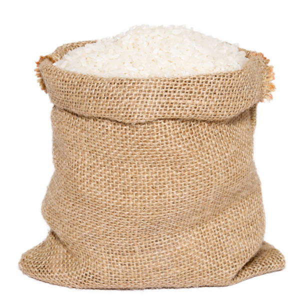 White rice in burlap sack bag isolated on white background stock photo