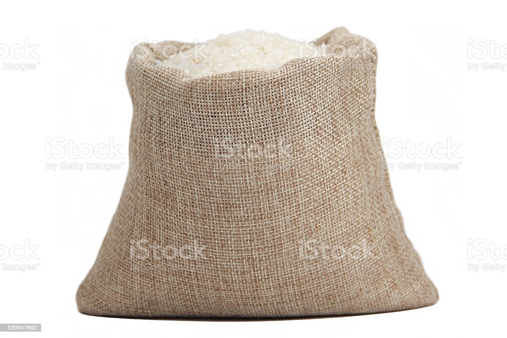 White rice in burlap sack isolated on white background stock photo