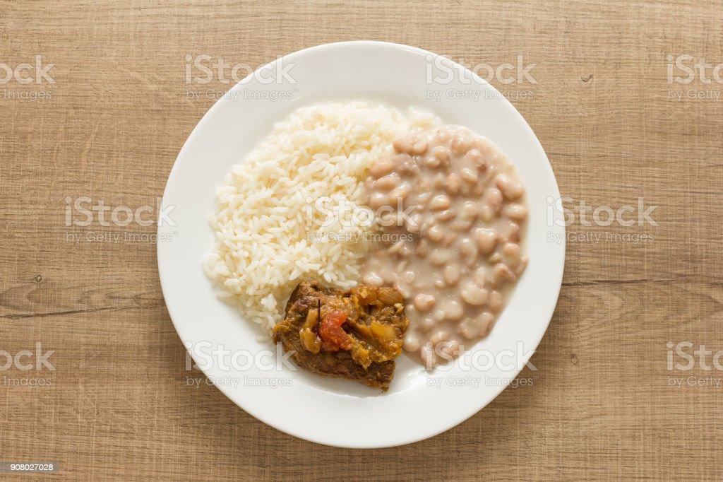 Arroz branco, feijão e carne com molho. Prato na mesa de madeira de branco. Sobrecarga, plana leigos de almoço. - foto de acervo
