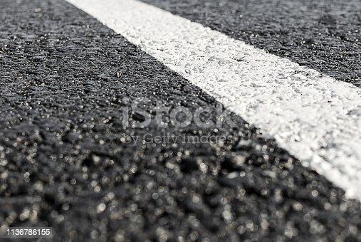 Road line on the wet asphalt close up. Concept of car traffic.