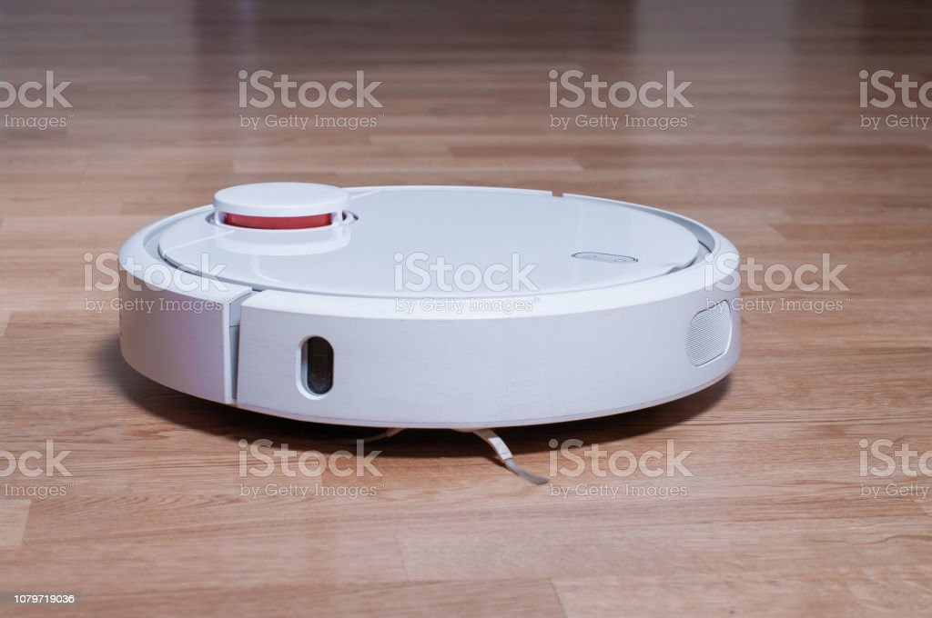 white robot vacuum cleaner on parquet floor cleaning dust in the room. smart robotic automate wireless cleaning technology housekeeping stock photo