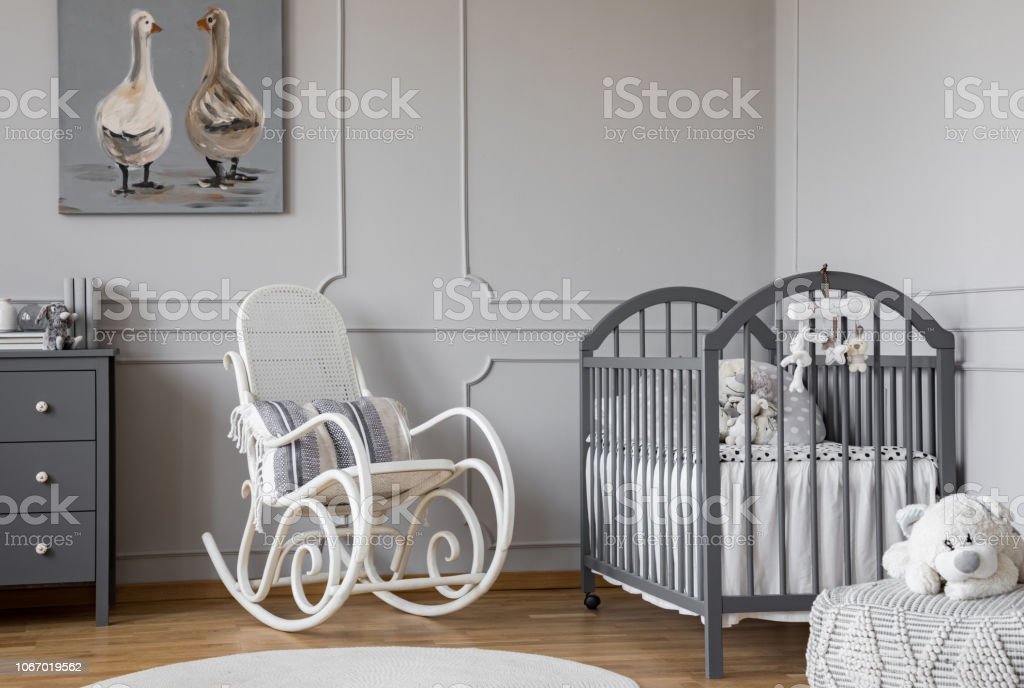 White rocking chair with pillow next to wooden cradle in elegant baby...
