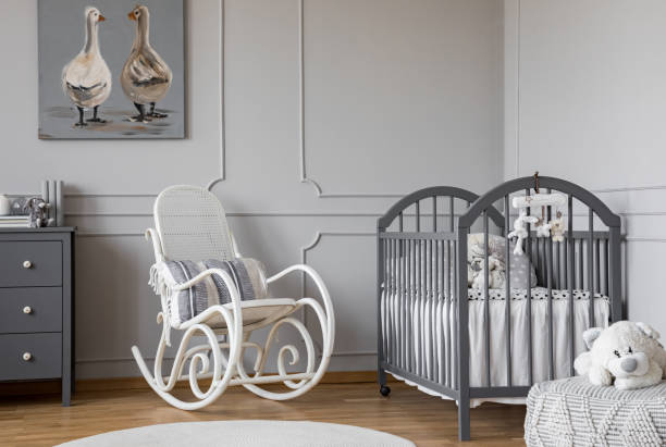 White rocking chair with pillow next to wooden cradle in elegant baby room with duck's poster on the wall stock photo