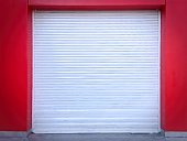 White Roll-up Door on Red Wall of the Garage