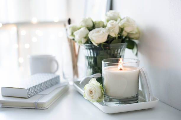 White room interior decor with burning hand-made candle and bouq stock photo