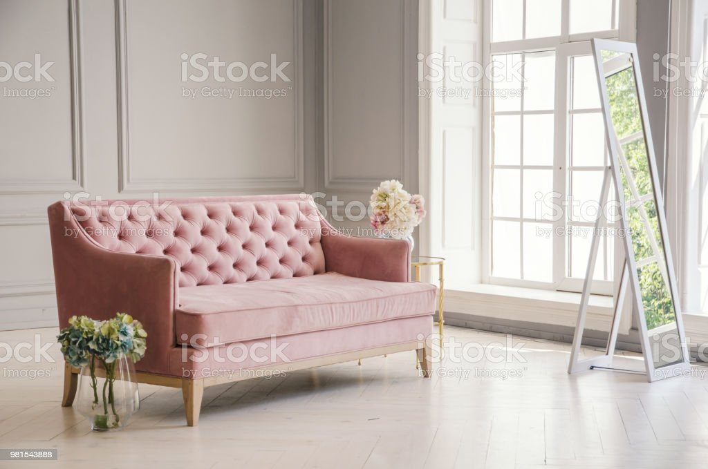 White Room With Pink Sofabed Flowers In Glass Jug And Mirror Near