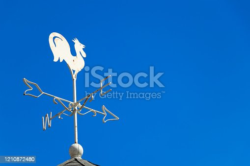 870218154 istock photo White rooster weather vane show the wind direction on blue sky background 1210872480