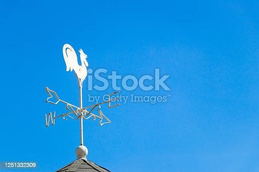 870218154 istock photo White rooster weather vane show the wind direction on blue sky background 1251332309