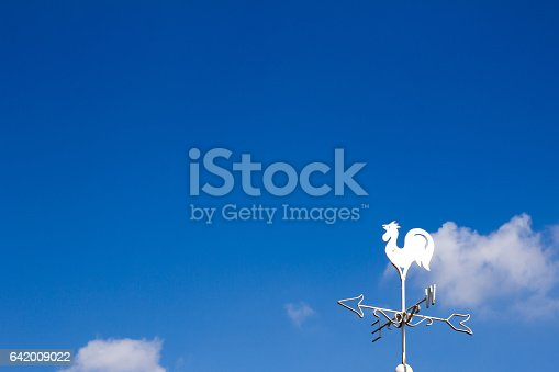 870218154 istock photo White rooster weather vane show the wind direction on blue sky background 642009022