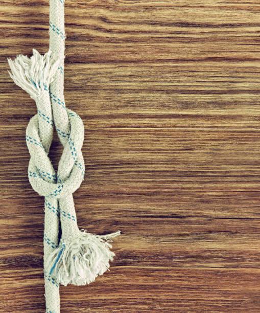 weißen seil und nautischen kreuzknoten auf hölzernen grunge hintergrund. - spleißen stock-fotos und bilder